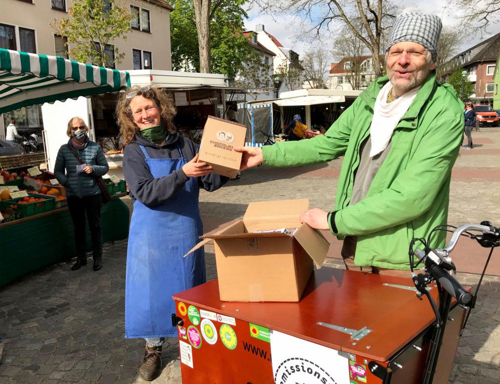 Klaus-Peter von der Schokofahrt überreicht Schokolade an Anne vom Ökomarkt